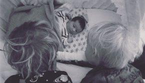 Baby Wieger in zijn wieg met broers